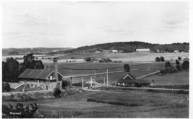 Till vänster Horreds mejeri och till höger smedjan. I bakgrunden Istorp. Långt bort till vänster skymtar Öxnevalla kyrka. Vägen bakom smedjan går till Istorp och vägen till  höger mot Horreds järnvägsstation. Bilden är troligen från 1950-talet.