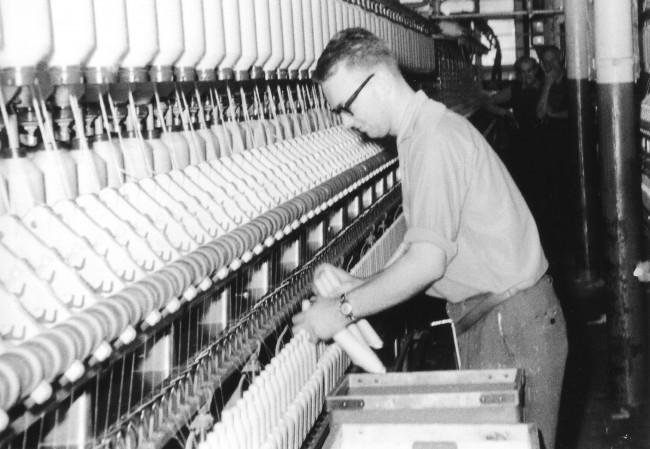 Ronny Johansson i färd med att skifta en spinnerimaskin