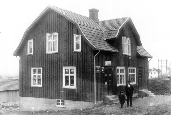 Carl Anderssons lanthandel. Carl och sonen Lennart framför det till synes nybyggda huset med affären omkring 1928. Bostaden fanns på andra våningen. Gården Annelunds bostadshus till höger i bakgrunden. Foto från Lennart Risenmark.