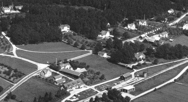 Skomakeriet är det lilla vita huset mitt i bilden intill landsvägen Varberg – Borås. Till höger därom ligger Framnäs hus. Nertill skymtar stationsområdet med bl.a. Ekelunds med kontor och lager. Foto från 1930-talet.