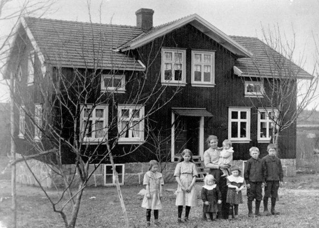 Lotta med barnen framför hemmet på Näverås. Foto troligen från våren 1915.