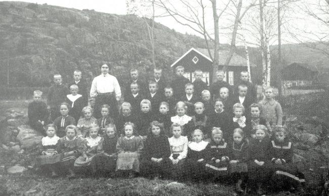 Vasse småskola med lärarinna och elever, ca 1911. I bakgrunden till höger skymtar frörenseriet vid Vasse damm.